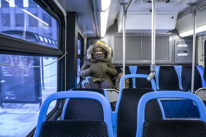 Lisa Laws is bundled up as she has a CTA bus to herself early Wednesday, Jan. 30, 2019.  The cold struck Chicago transportation Wednesday morning, with more than 1,600 canceled flights and limited rail service.  (Rich Hein/Chicago Sun-Times via AP)