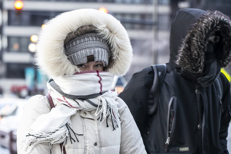 A bundled-up commuter makes their way through the loop early Wednesday, Jan. 30, 2019 in Chicago. A deadly arctic deep freeze enveloped the Midwest with record-breaking temperatures triggering widespread closures of schools and businesses.  (Rich Hein/Chicago Sun-Times via AP)