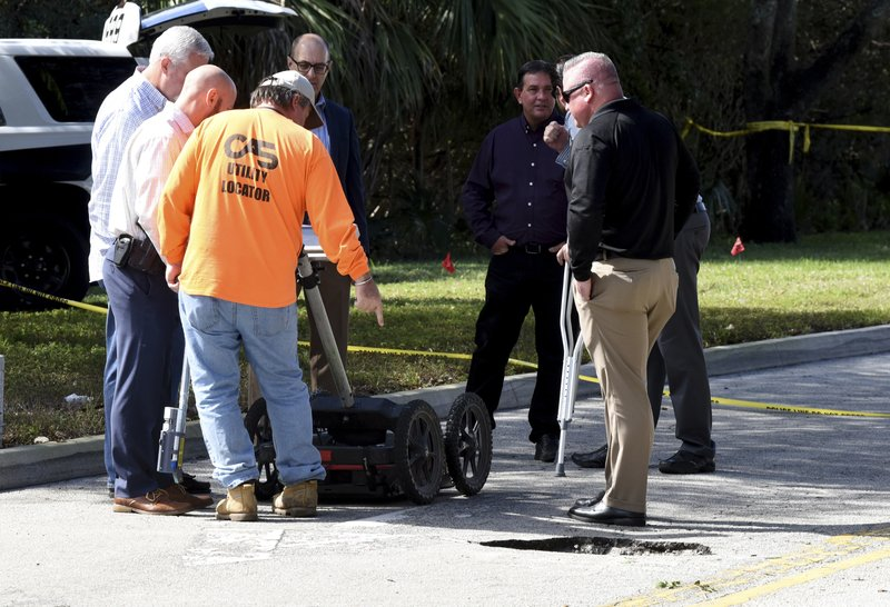 FBI and Pembroke Pines Police look at a tunnel by a possible would-be bank robber which was discovered beneath the entrance to the Flamingo Pines shopping plaza Wednesday, Jan. (Taimy Alvarez/South Florida Sun-Sentinel via AP)