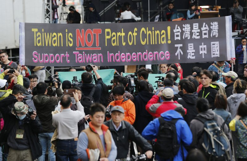 FILE - In this Jan. 16, 2016, file photo, pro-independence supporters carry a banner shouting that Taiwan is not part of China outside the Democratic Progressive Party presidential campaign headquarters in Taipei, Taiwan. (AP Photo/Wally Santana, File)