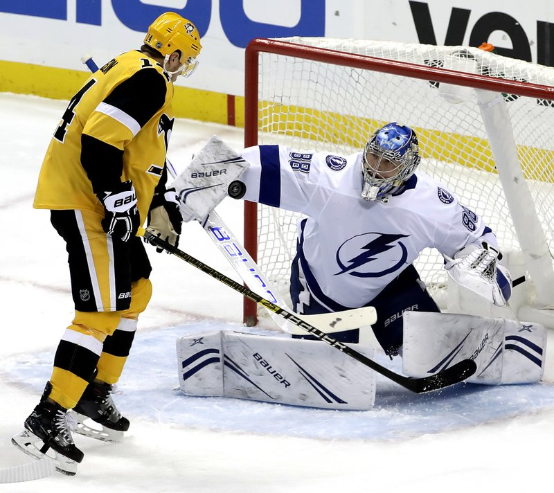 Tampa Bay Lightning goaltender Andrei Vasilevskiy (88) blocks a shot with Pittsburgh Penguins' Tanner Pearson (14) looking for the rebound during the first period of an NHL hockey game in Pittsburgh, Wednesday, Jan. (AP Photo/Gene J. Puskar)
