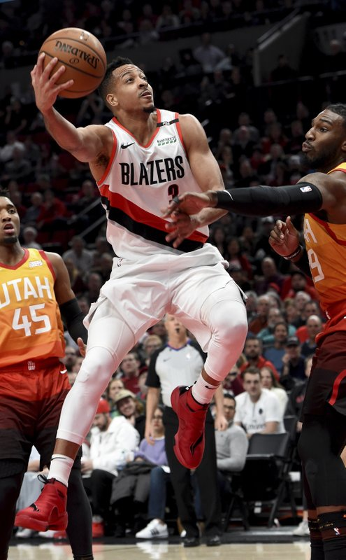 Portland Trail Blazers guard CJ McCollum, center, drives to the basket on Utah Jazz guard Donovan Mitchell, left and forward Jae Crowder, right, during the second half of an NBA basketball game in Portland, Ore. (AP Photo/Steve Dykes)