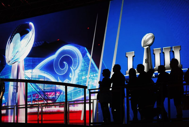 Fans line up in front of a big screen to have their photo taken with the Vince Lombardi Trophy on display at the NFL Experience ahead of Sunday's Super Bowl 53 football game between the Los Angeles Rams and New England Patriots in Atlanta, Wednesday, Jan. (AP Photo/David Goldman)