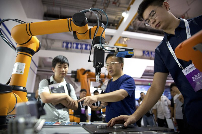 FILE - In this Aug. 18, 2018, file photo, visitors look at a manufacturing robot from Chinese robot maker Aubo Robotics at the World Robot Conference in Beijing, China. (AP Photo/Mark Schiefelbein, File)