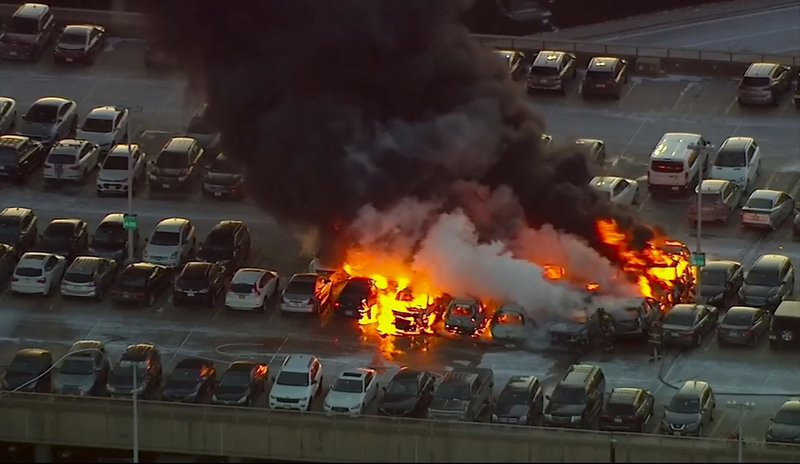 In this image from video made available by WABC-TV, firefighters work at the scene of several burning vehicles on top of a parking garage at Newark Liberty International Airport on Thursday, Jan. (WABC-TV via AP)