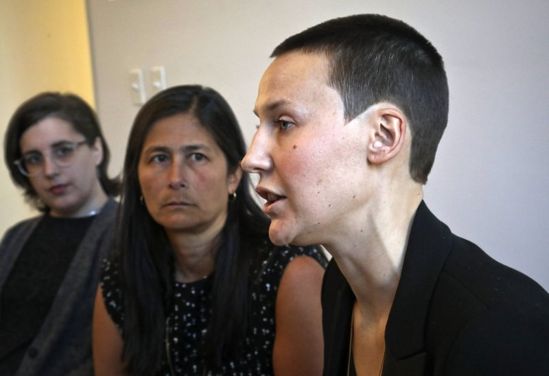 Alison Turkos, right, speaks as Jennifer Welch Demski, left, and attorney Mariann Wang, center, listen during a news conference to discuss their lawsuit against the New York Police Department for
