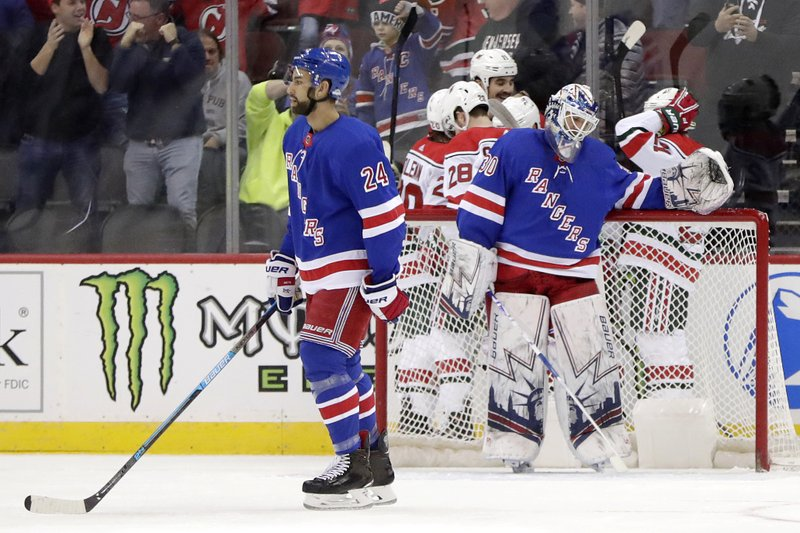 New York Rangers goaltender Henrik Lundqvist, right, of Sweden, reacts as New Jersey Devils players celebrate a goal by Marcus Johansson (90), also of Sweden, during the first period of an NHL hockey game, Thursday, Jan. (AP Photo/Julio Cortez)