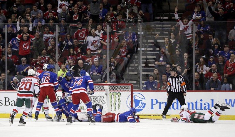 New Jersey Devils left wing Marcus Johansson, right, of Sweden, falls forward while scoring a goal on the New York Rangers during the first period of an NHL hockey game, Thursday, Jan. (AP Photo/Julio Cortez)