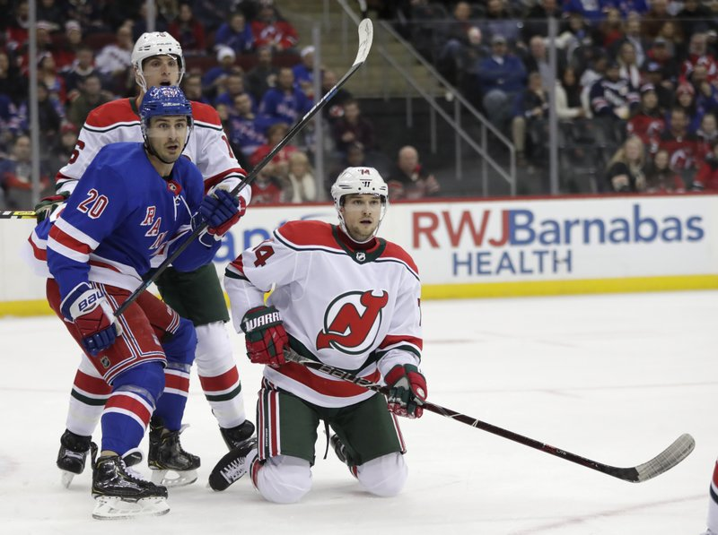New Jersey Devils defenseman Egor Yakovlev, right, of Russia, is unable to get back on his feet after losing a blade to his right skate while defending against the New York Rangers during the first period of an NHL hockey game, Thursday, Jan. (20) and defenseman Steven Santini (16) look on during the play. (AP Photo/Julio Cortez)