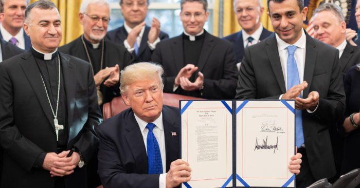 President Donald J. Trump is joined by legislators and Archbishop Bashar Warda of Erbil-Kurdistan, Iraq, left, as he signs H.R. 390-Iraq and Syria Genocide Relief and Accountability Act of 2018 Tuesday, Dec. 11, 2018 in the Oval Office of the White House. (Official White House Photo by Shealah Craighead)