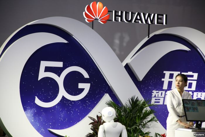FILE - A woman stands at the booth of Huawei featuring 5G technology at the P