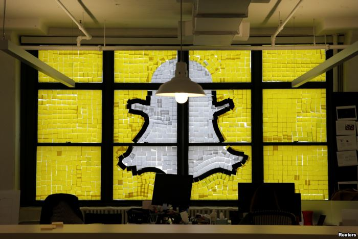 FILE - An image of the Snapchat logo created with Post-it notes is seen in lo