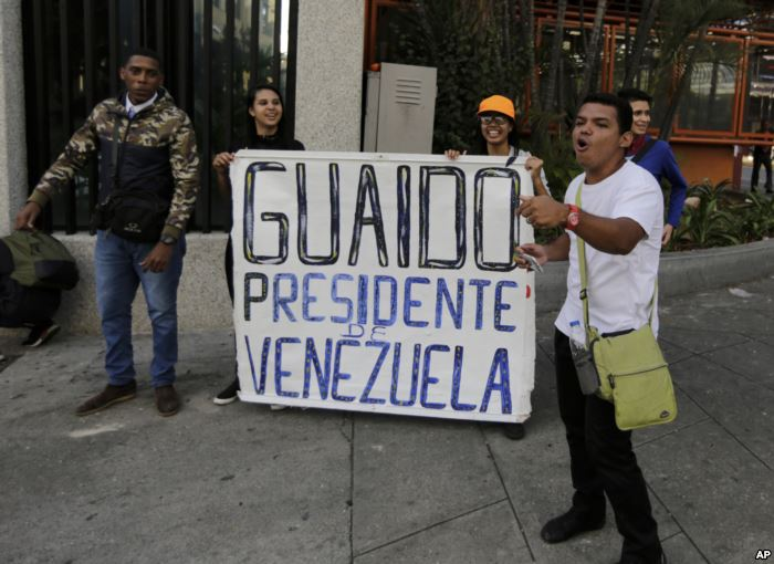"FILE - Anti-government protesters show a sign reading in Spanish ""Guaido"