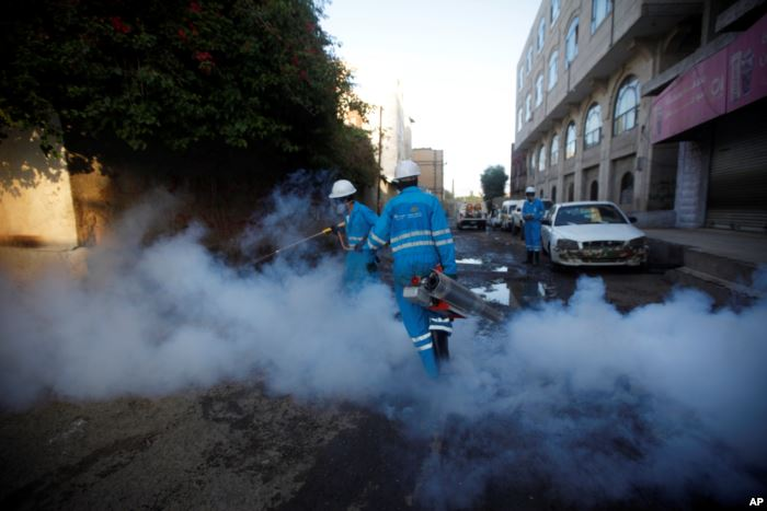 FILE - Public health workers spray insecticide amid fears of a new cholera ou