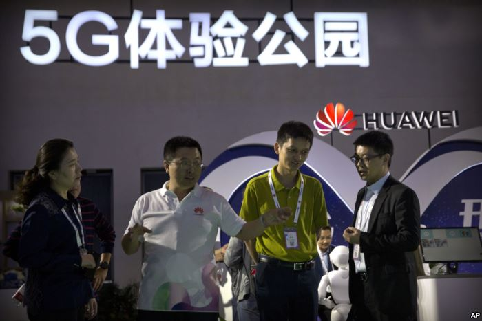 FILE - Visitors look at a display for 5G wireless technology from Chinese tec