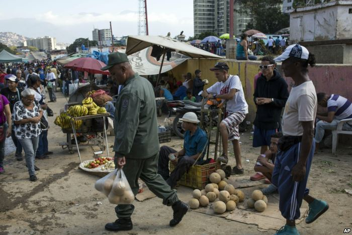 Workers and customers gather at a wholesale food market in Caracas, Venezuela