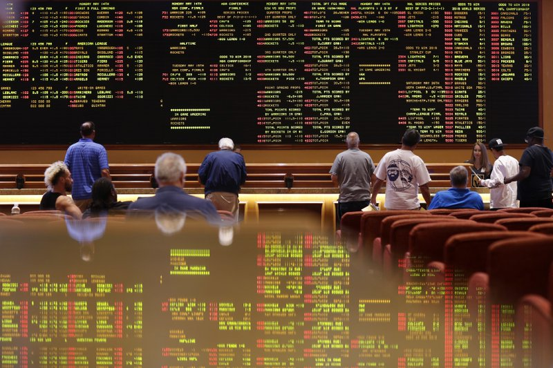 FILE - In this May 14, 2018 file photo, people make bets in the sports book at the South Point hotel and casino in Las Vegas. (AP Photo/John Locher, File)