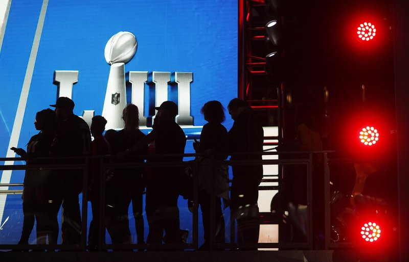 Fans line up to have their photo taken with the Vince Lombardi Trophy on display at the NFL Experience ahead of Sunday's Super Bowl 53 football game between the Los Angeles Rams and New England Patriots in Atlanta, Wednesday, Jan. (AP Photo/David Goldman)