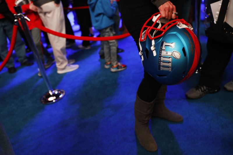 A fan holds a commemorative helmet while waiting in line to have a photo taken with the Vince Lombardi Trophy at the NFL Experience ahead of Sunday's Super Bowl 53 football game between the Los Angeles Rams and New England Patriots in Atlanta, Wednesday, Jan. (AP Photo/David Goldman)
