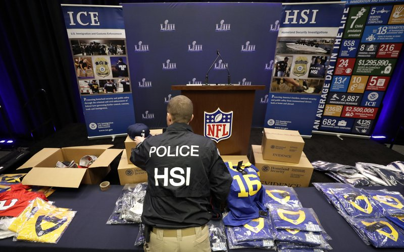 Homeland Security Investigations spokesman Bryan Cox unpacks some of the counterfeit items seized for the NFL Super Bowl 53 football game before a news conference Thursday, Jan. (AP Photo/David J. Phillip)