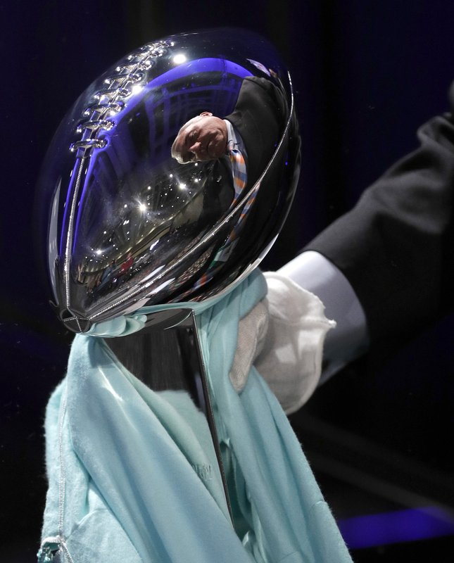 NFL Security's Joe Persichini Jr. is reflected in the Vince Lombardi Trophy as he prepares it for display before a news conference for the NFL Super Bowl 53 football game Wednesday, Jan. (AP Photo/David J. Phillip)