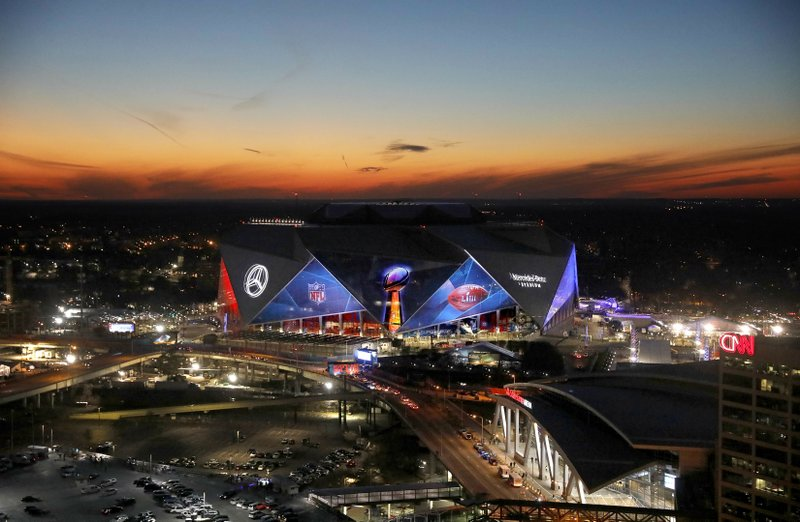 The sun sets behind Mercedes-Benz Stadium ahead of Sunday's NFL Super Bowl 53 football game between the Los Angeles Rams and New England Patriots in Atlanta, Wednesday, Jan. (AP Photo/David Goldman)