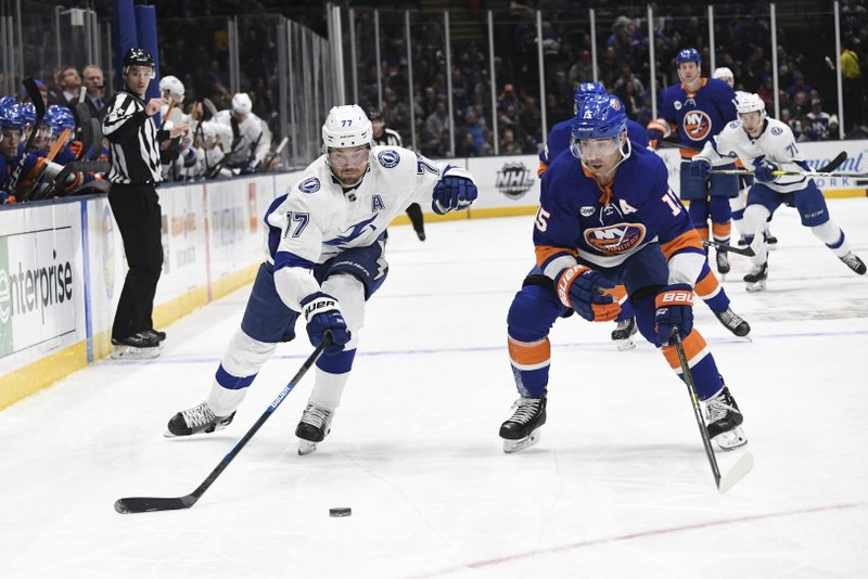 Tampa Bay Lightning's Victor Hedman (77) and New York Islanders' Cal Clutterbuck (15) skate to the puck during the first period of an NHL hockey game Friday, Feb. (AP Photo/Kathleen Malone-Van Dyke)