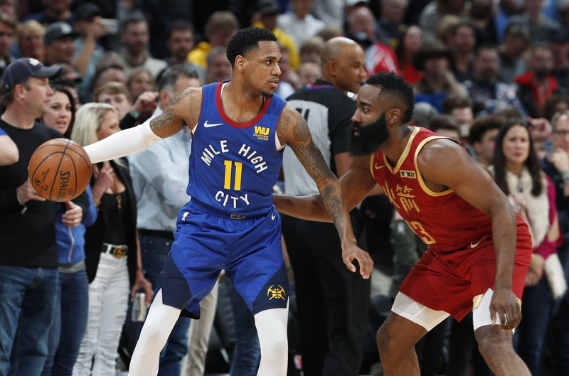 Denver Nuggets guard Monte Morris, left, looks to pass the ball as Houston Rockets guard James Harden defends during the first half of an NBA basketball game Friday, Feb. (AP Photo/David Zalubowski)