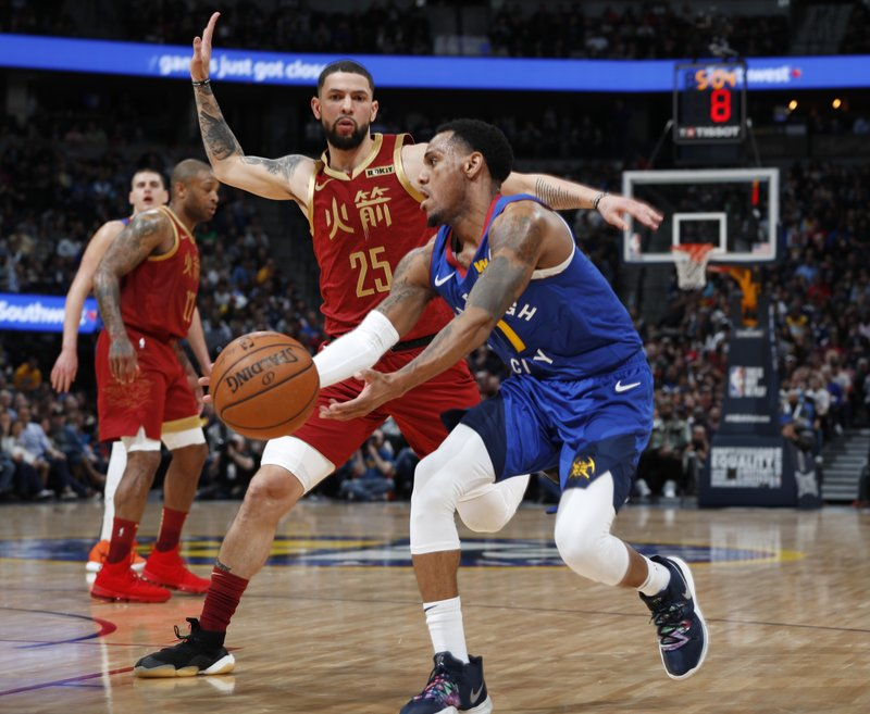 Denver Nuggets guard Monte Morris front, looks to pass the ball as Houston Rockets guard Austin Rivers defends during the second half of an NBA basketball game Friday, Feb. (AP Photo/David Zalubowski)