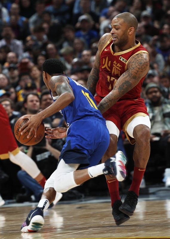 Denver Nuggets guard Monte Morris, left, tries to drive past Houston Rockets forward PJ Tucker in the first half of an NBA basketball game Friday, Feb. (AP Photo/David Zalubowski)