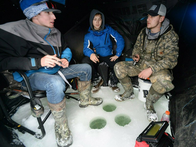 In this Saturday, Jan. 26, 2019 photo, friends, from left, Luke Soboleski, 19, Hunter Klobucar, 20, and Tyler Waltenbaugh, 22, sit inside their hut on Misery Bay while ice fishing at Presque Isle State Park near Erie, Pa. (Greg Wohlford/Erie Times-News via AP)