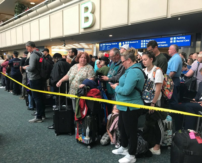 People wait to get through security at the Orlando International Airport following a security incident on Saturday, Feb. (Jonathan Hayward/The Canadian Press via AP)