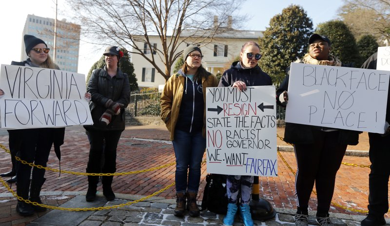 Demonstrators hold signs and chant outside the Governors Mansion at the Capitol in Richmond, Va., Saturday, Feb. (AP Photo/Steve Helber)