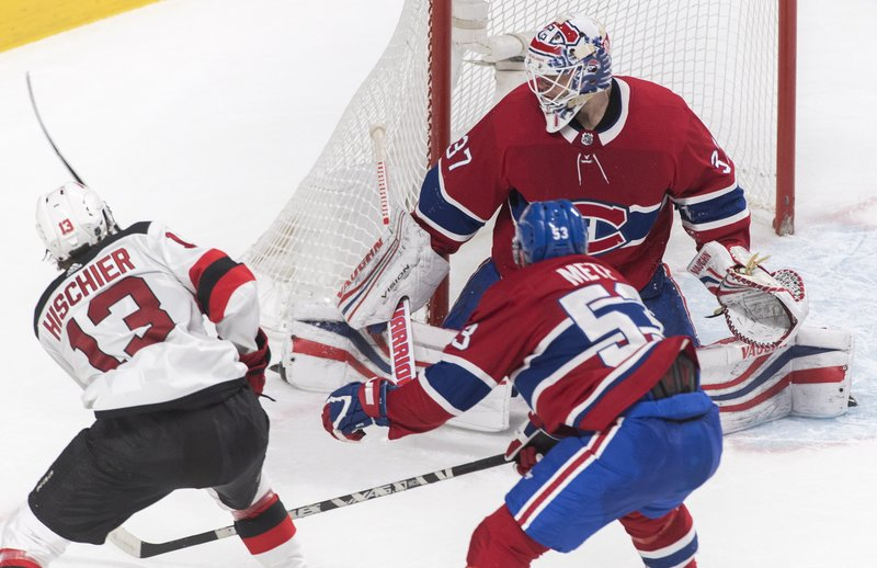 New Jersey Devils' Nico Hischier (13) scores against Montreal Canadiens goaltender Antti Niemi as Canadiens' Victor Mete defends during the third period of an NHL hockey game, Saturday, Feb. (Graham Hughes/The Canadian Press via AP)