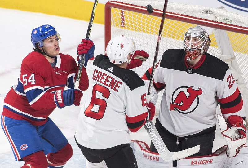 Montreal Canadiens' Charles Hudon (54) moves in on New Jersey Devils goaltender Mackenzie Blackwood as Devils' Andy Greene defends during the second period of an NHL hockey game, Saturday, Feb. (Graham Hughes/The Canadian Press via AP)