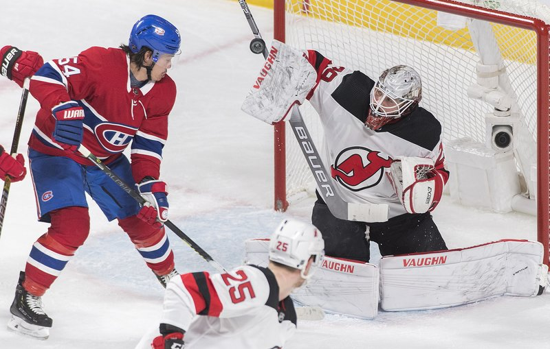 Montreal Canadiens' Charles Hudon (54) moves in on New Jersey Devils goaltender Mackenzie Blackwood as Devils' Mirco Mueller (25) defends during the second period of an NHL hockey game, Saturday, Feb. (Graham Hughes/The Canadian Press via AP)