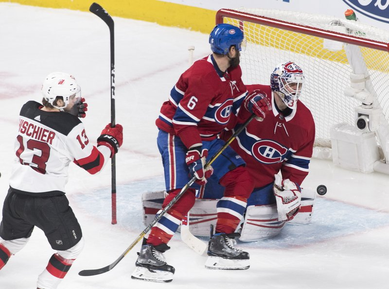 New Jersey Devils' Nico Hischier scores against Montreal Canadiens goaltender Antti Niemi as Canadiens' Shea Weber defends during the third period of an NHL hockey game, Saturday, Feb. (Graham Hughes/The Canadian Press via AP)
