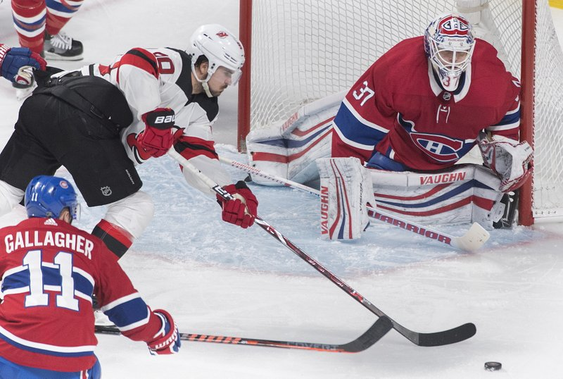 New Jersey Devils' Marcus Johansson (90) moves in on Montreal Canadiens goaltender Antti Niemi as Canadiens' Brendan Gallagher defends during the third period of an NHL hockey game, Saturday, Feb. (Graham Hughes/The Canadian Press via AP)