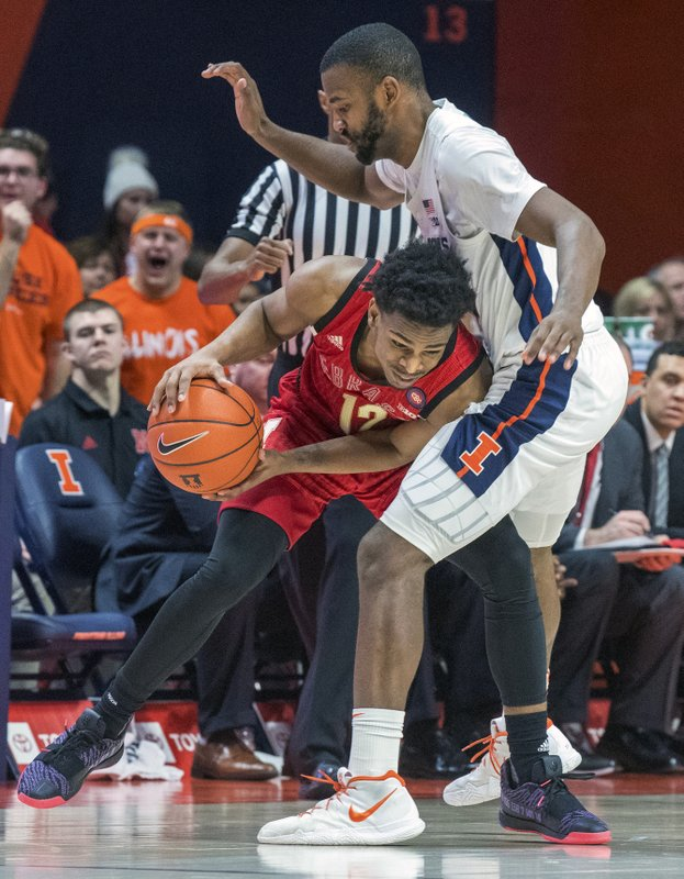 Nebraska guard Thomas Allen (12) drives into Illinois guard Aaron Jordan (23) during the second half of an NCAA college basketball game in Champaign, Ill. (AP Photo/Robin Scholz)