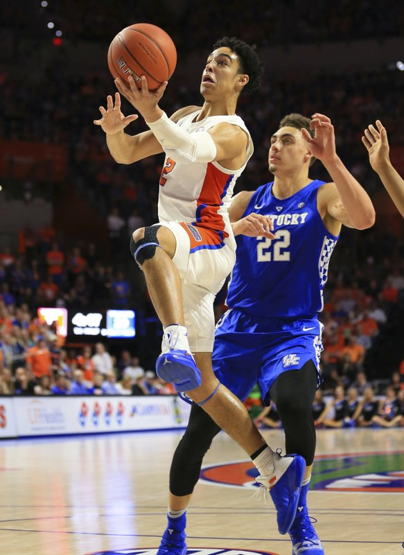 Florida guard Andrew Nembhard makes a layup past Kentucky forward Reid Travis during the first half of an NCAA college basketball game Saturday, Feb. (AP Photo/Matt Stamey)