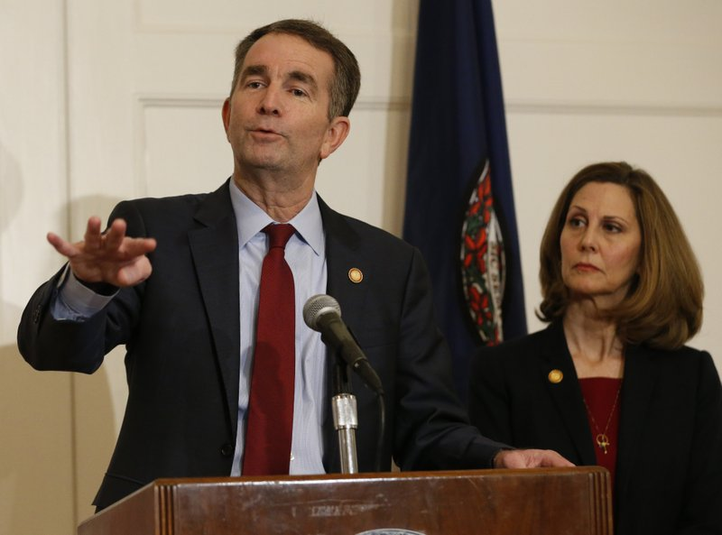 Virginia Gov. Ralph Northam, left, gestures as his wife, Pam, listens during a news conference in the Governors Mansion at the Capitol in Richmond, Va. (AP Photo/Steve Helber)