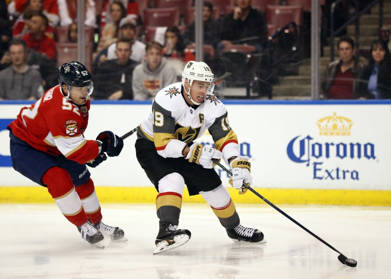 Vegas Golden Knights right wing Reilly Smith (19) skates to the net followed by Florida Panthers defenseman MacKenzie Weegar (52) during the first period of an NHL hockey game, Saturday, Feb. (AP Photo/Wilfredo Lee)
