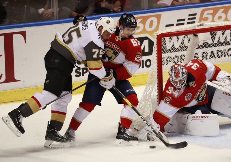 Vegas Golden Knights right wing Ryan Reaves (75) attempts to shoot at Florida Panthers goaltender James Reimer (34) and center Denis Malgin (62) during the second period of an NHL hockey game, Saturday, Feb. (AP Photo/Wilfredo Lee)