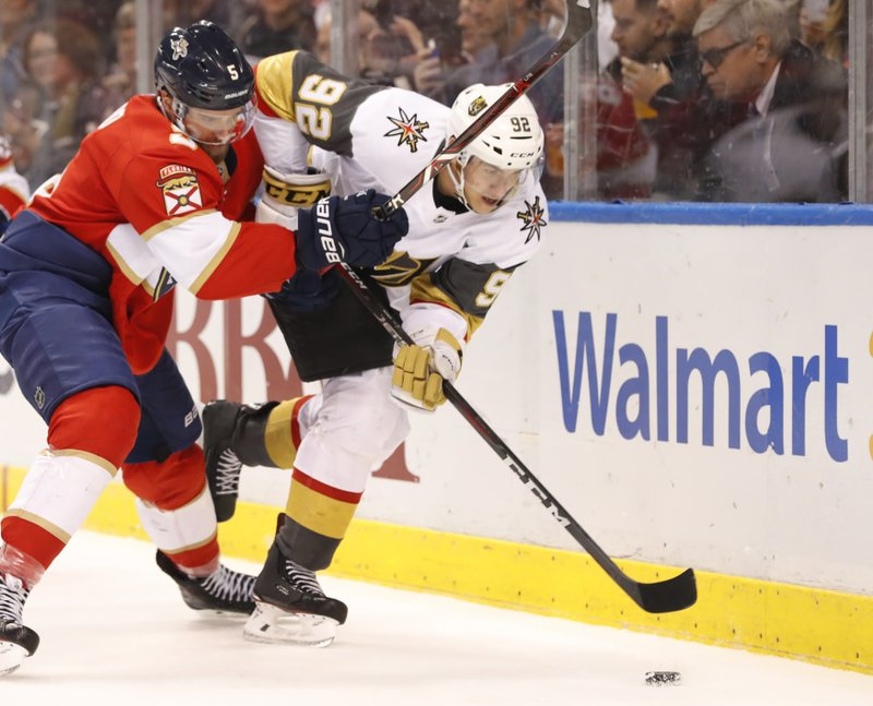 Florida Panthers defenseman Aaron Ekblad (5) and Vegas Golden Knights left wing Tomas Nosek (92) battle for the puck during the first period of an NHL hockey game, Saturday, Feb. (AP Photo/Wilfredo Lee)