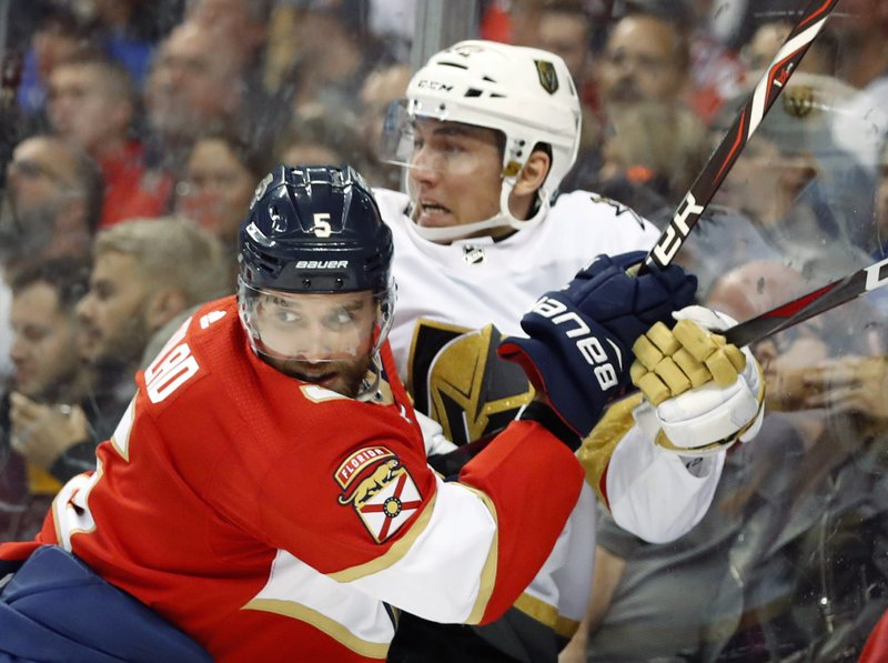 Florida Panthers defenseman Aaron Ekblad (5) slams Vegas Golden Knights left wing Tomas Nosek into the boards during the first period of an NHL hockey game, Saturday, Feb. (AP Photo/Wilfredo Lee)
