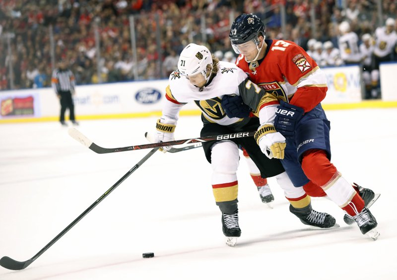 Vegas Golden Knights center William Karlsson (71) and Florida Panthers defenseman Mark Pysyk (13) battle for the puck during the first period of an NHL hockey game, Saturday, Feb. (AP Photo/Wilfredo Lee)