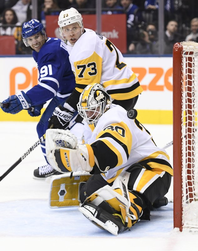 Pittsburgh Penguins goaltender Matt Murray (30) lets in a goal from Toronto Maple Leafs left wing Zach Hyman, not shown, as Toronto Maple Leafs center John Tavares (91) and Pittsburgh Penguins defenseman Jack Johnson (73) look on during the second period of an NHL hockey game, Saturday, Feb. (Nathan Denette/The Canadian Press via AP)