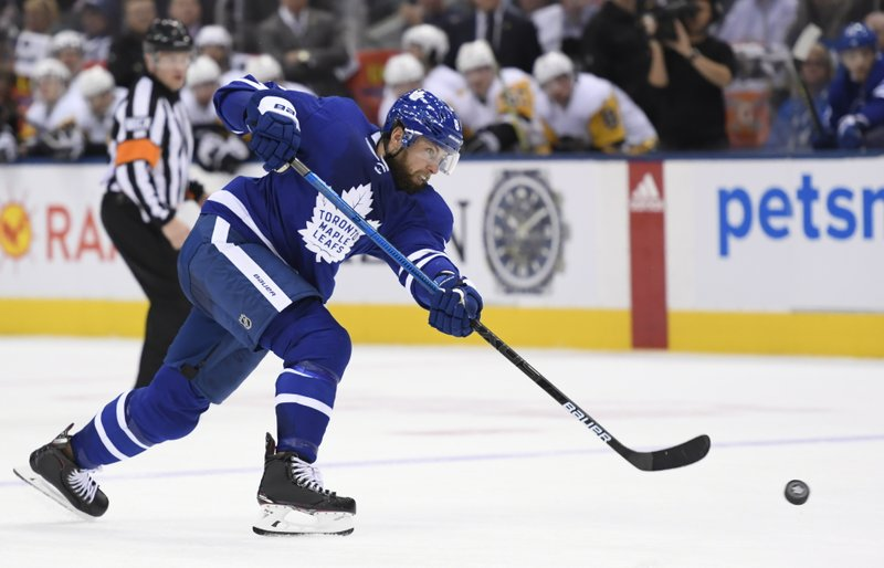 Toronto Maple Leafs newly acquired defenseman Jake Muzzin (8) takes a first timer shot during the second period of an NHL hockey game against the Pittsburgh Penguins, Saturday, Feb. (Nathan Denette/The Canadian Press via AP)