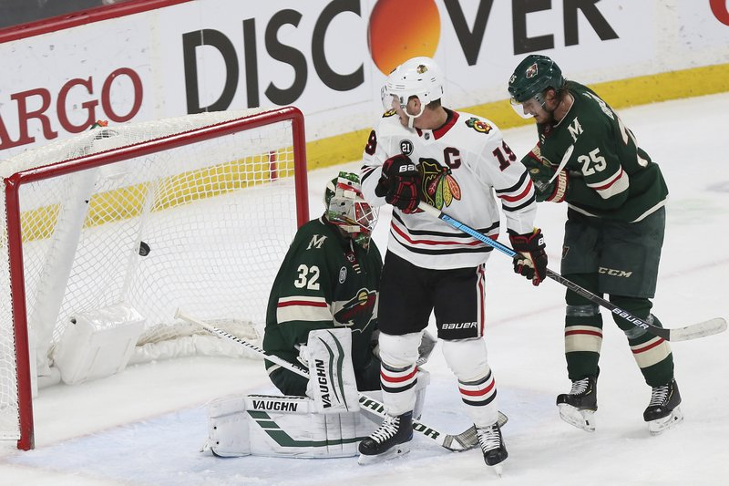 Chicago Blackhawks' Jonathan Toews looks back at the net to see the overtime goal by Erik Gustafsson against Minnesota Wild goalie Alex Stalock during an NHL hockey game Saturday, Feb. (AP Photo/Stacy Bengs)