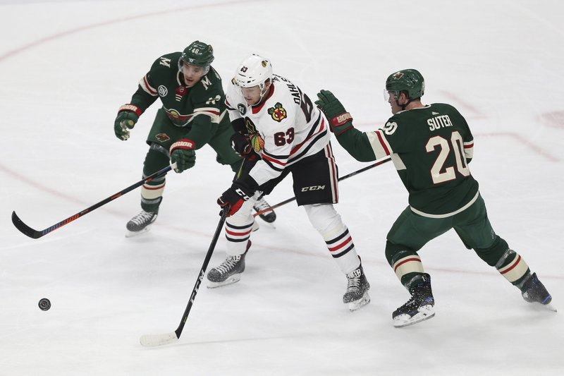 Chicago Blackhawks' Carl Dahlstrom tries to control the puck against Minnesota Wild's Jason Zucker and Ryan Suter during the first period of an NHL hockey game Saturday, Feb. (AP Photo/Stacy Bengs)